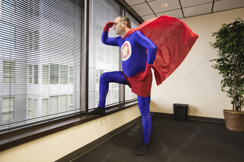 Office superhero at window, ponders his next business move