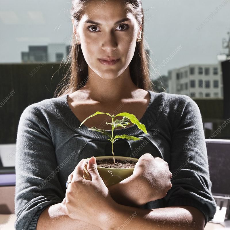 woman holding a house plant in an office cubicle
