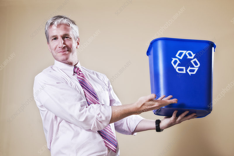 Man in shirt and tie holding a recycle waste bin