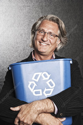 Portrait of actor holding a blue recycling bin to his chest