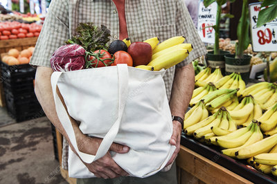 Person at food market, with shopping bag of fresh produce