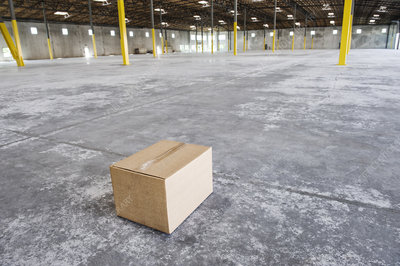 Single cardboard box in a new empty warehouse space