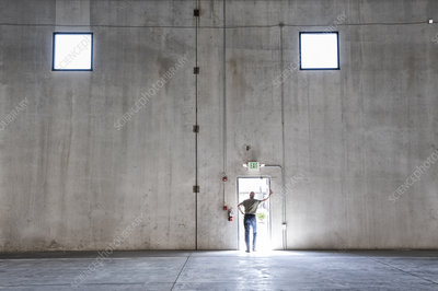 Worker standing silhouetted in doorway of new warehouse
