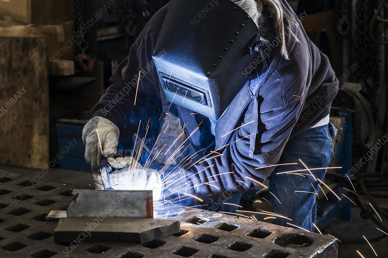 Worker using Oxyacetylene gas to weld in sheet metal factory