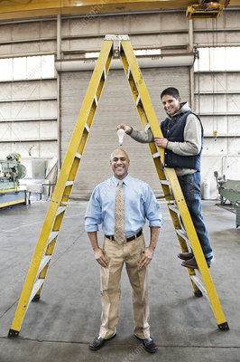 Owner and worker goofing off together in sheet metal factory