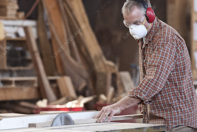 Worker wearing hearing protection and mask, cutting wood