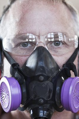 Factory worker wearing safety glasses and respirator