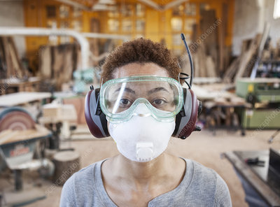 Worker wearing safety glasses and mask in a factory