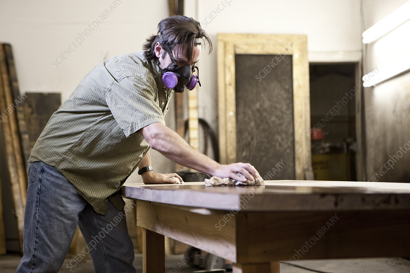 Worker applying finish stain to table in woodworking factory