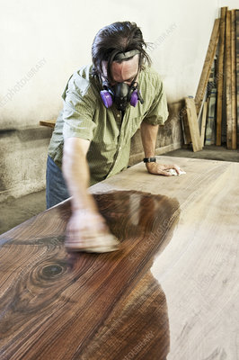 Worker applying finish to recycled wood table top