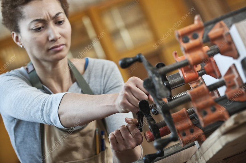 Woman worker adjusting clamps in a woodworking factory