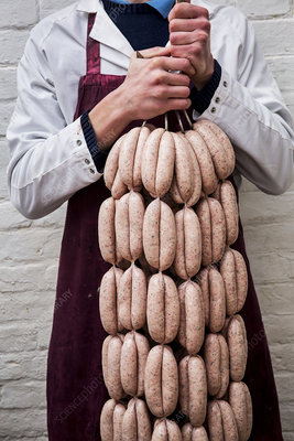 Man holding freshly made sausages hanging from hooks