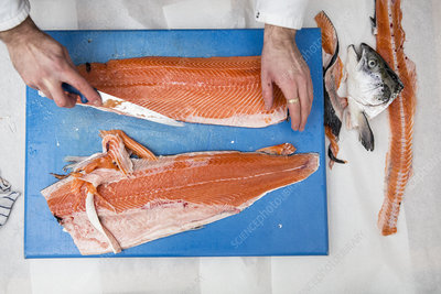 Fishmonger cutting and filleting fresh salmon