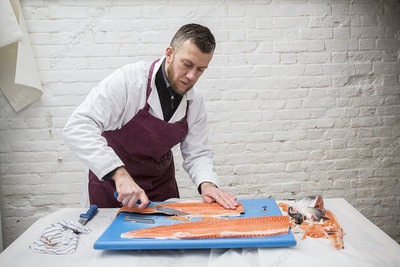 Man filleting fresh salmon on blue chopping board