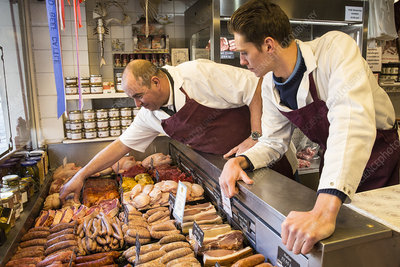 Two men wearing aprons standing in a butcher shop