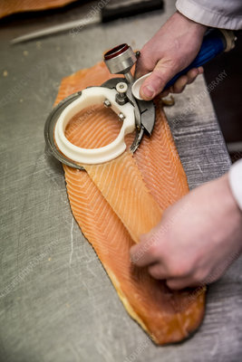 Fishmonger using special slicer to slice fillet of salmon