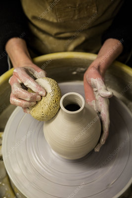 Potter wearing apron shaping clay vase on pottery wheel