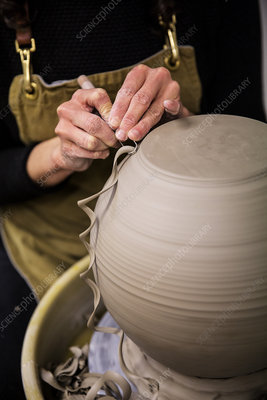 Potter working on spherical clay vase on pottery wheel