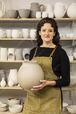Woman wearing apron holding unfired spherical clay vase