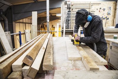 Man in a warehouse, sanding planks of recycled wood