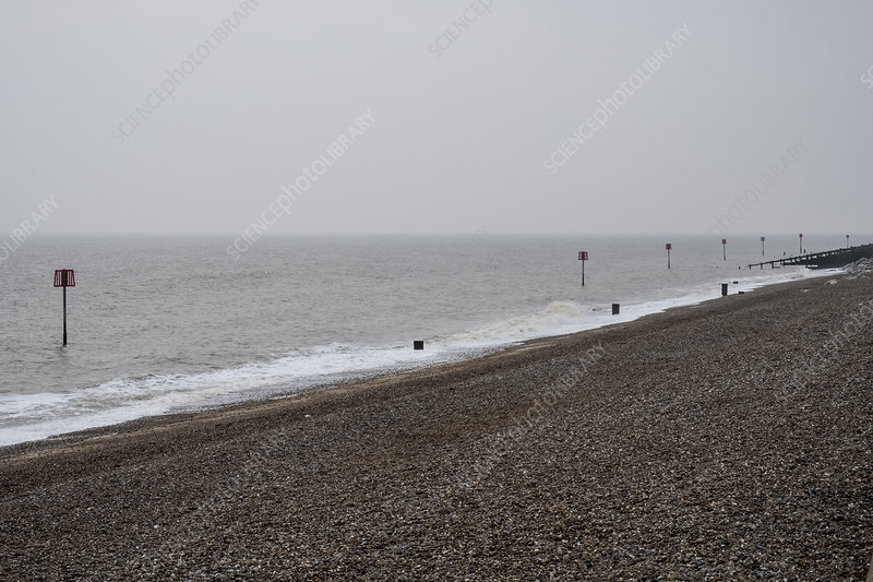 Shingle beach with a row of partially submerged metal poles