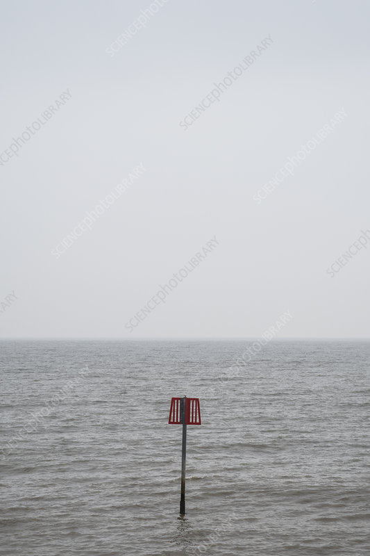 Partially submerged metal marker pole in the ocean