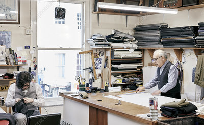 Father and son making suits in family-run tailor business