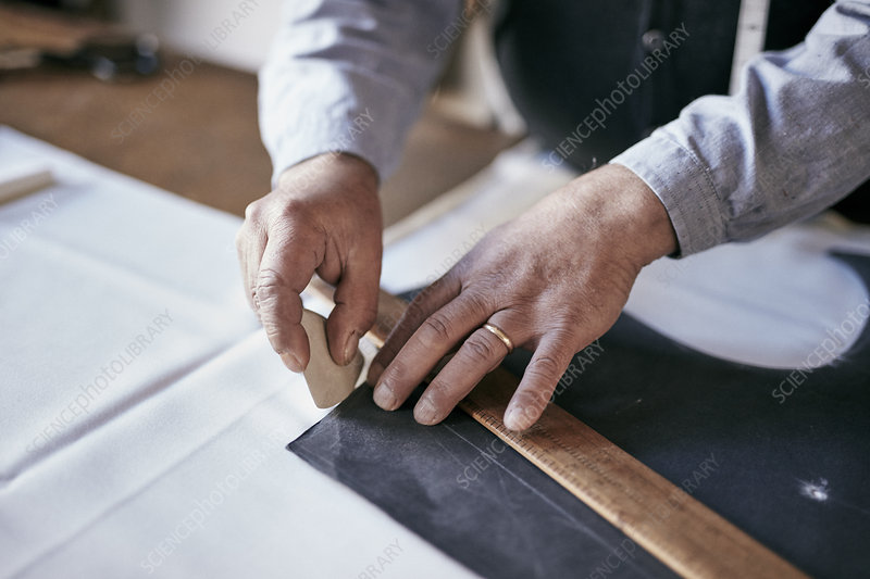 Tailor using chalk and ruler to outline pattern on fabric