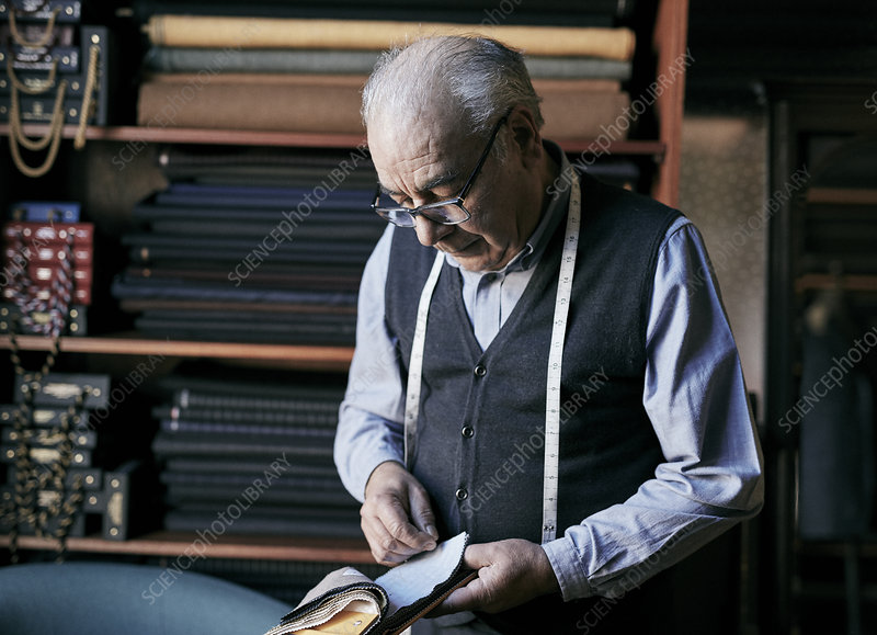 Tailor inspecting fabric samples