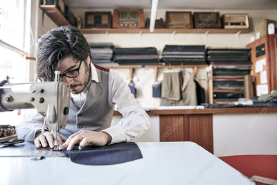 Man sewing a garment at a family tailoring business workshop