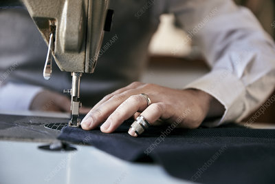 Man using an industrial sewing machine, stitching a garment