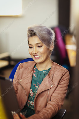 Smiling creative businesswoman using digital tablet