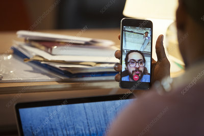 Businessman video chatting with colleague on smart phone