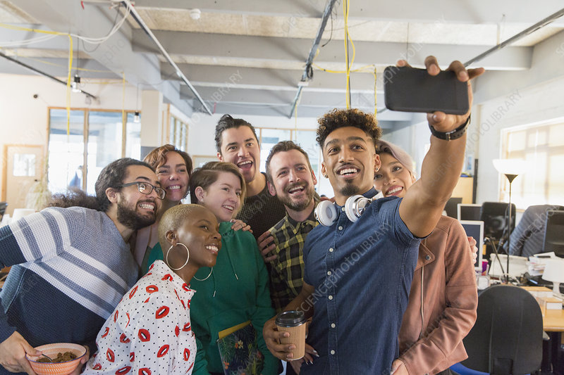 Creative business team taking selfie in office