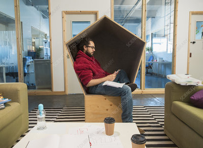 Creative businessman using smart phone in office cubby