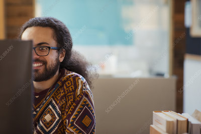 Smiling creative businessman working at computer
