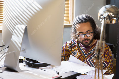 Businessman reading paperwork at computer in office