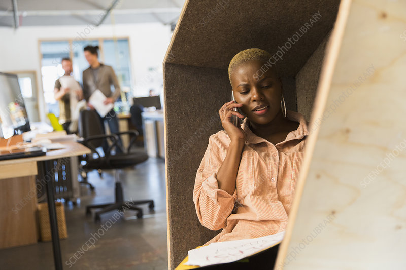 Businesswoman talking on smart phone in office cubby