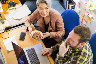 Business people eating cereal, working at laptop on office
