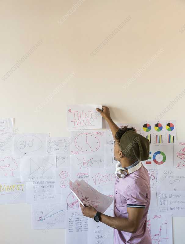 Creative businessman hanging paperwork on office wall