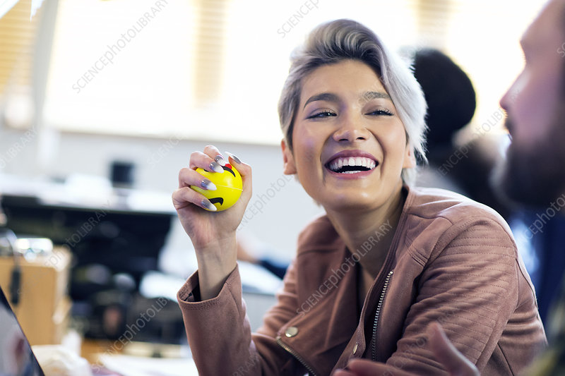 Laughing Businesswoman squeezing stress ball in office