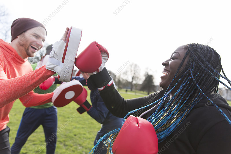 Enthusiastic friends boxing in park