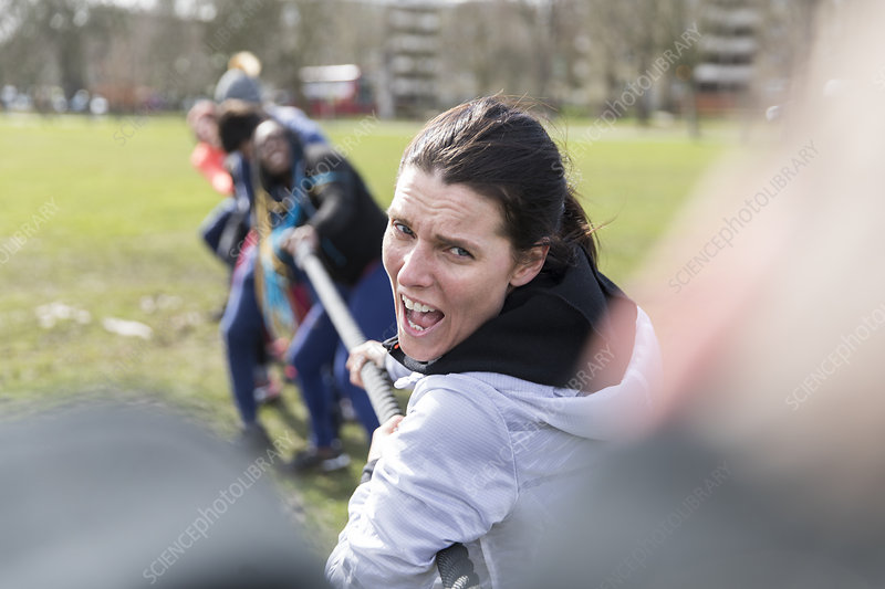 Determined woman enjoying tug-of-war in park