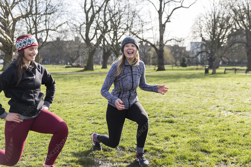 Smiling women doing lunges in sunny park