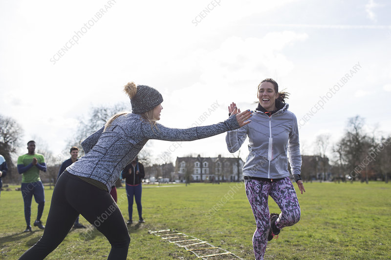 Women high-fiving, exercising in park