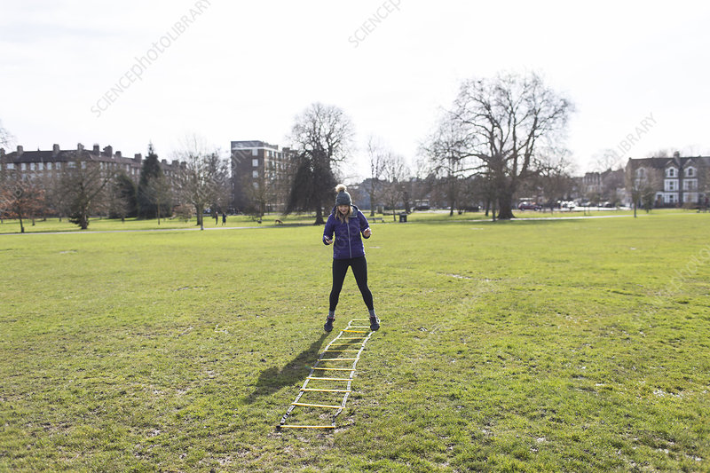 Woman exercising, doing speed ladder drill in sunny park