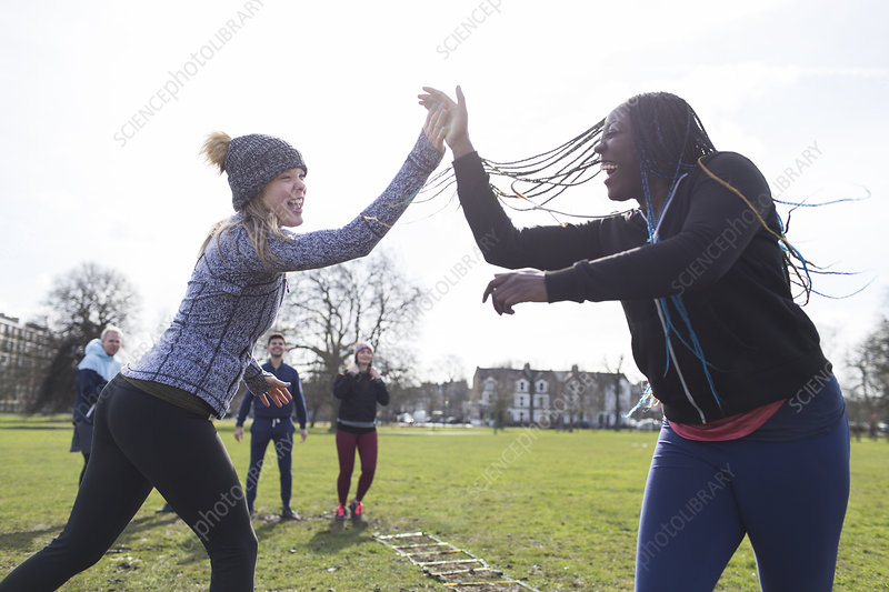 Enthusiastic women high-fiving, exercising in sunny park