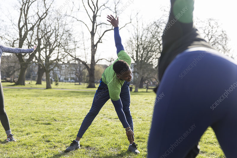 Man stretching, exercising in park