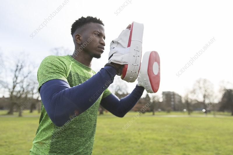 Focused man boxing in park