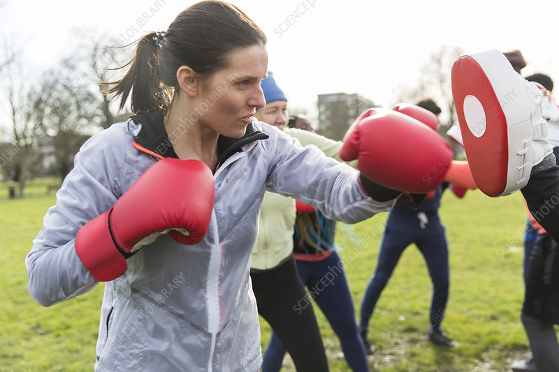 Determined, tough woman boxing in park